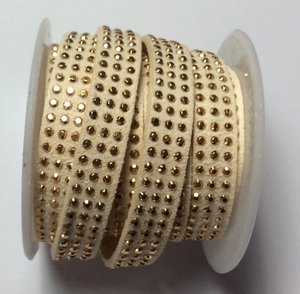 Syntetisk mocka med 3 rader guldbling, 10 mm bredd. Per 20 cm